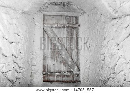 Vintage wooden door covered with hoarfrost conceptual entrance door in the winter season
