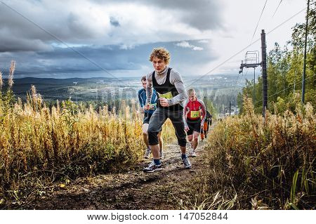 Revda Russia - September 10 2016: skyrunning group of runners running uphill on blue sky background during marathon Vertical kilometer