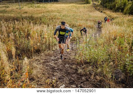 Revda Russia - September 10 2016: group of men runners skyrunners running uphill trail in grass during marathon Vertical kilometer