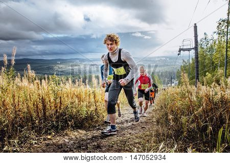 Revda Russia - September 10 2016: group of runners marathon runner ran uphill on blue sky background during marathon Vertical kilometer
