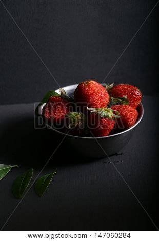 Strawberries in a bowl with dark background.