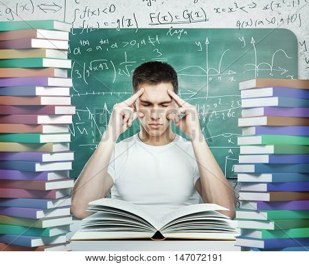 Pensive young man surrounded with piles of colorful book and mathematical formulas on chalkboard. Education concept