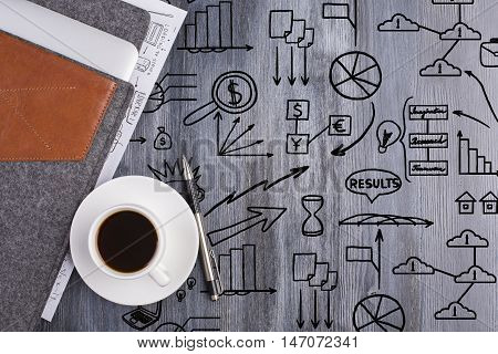 Top view of wooden desktop with creative black business doodles coffee cup electronic device in case and pen