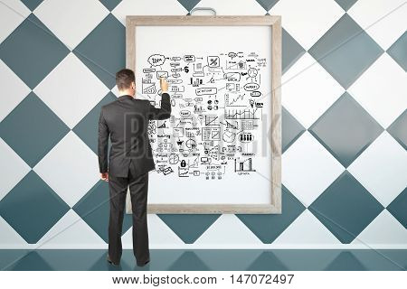 Back view of young businessman in suit drawing business sketch in picture frame. Success concept