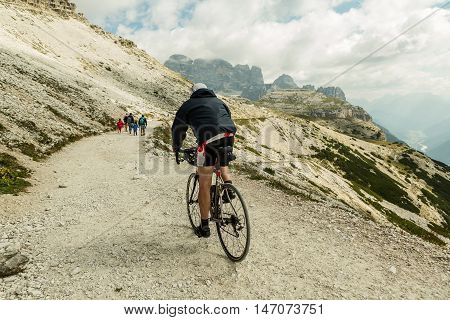 unknown biker on bike tour arround Drei Zinnen or Tre Cime di Lavaredo, Italian Dolomites. Travel concept, copy space, advertising