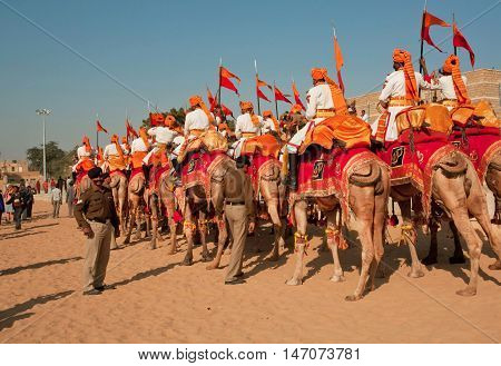 JAISALMER, INDIA - FEB 1, 2015: Colorful caravan of camel riders from Rajasthan military deportament on the great Desert Festival on February 1, 2015. Every winter Jaisalmer takes the famous Desert Festival
