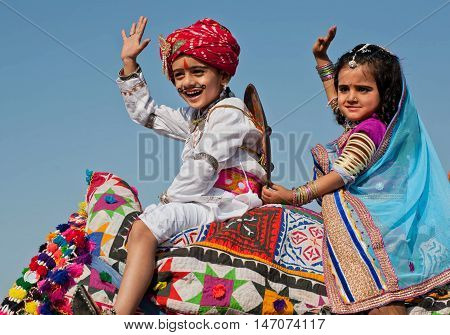 JAISALMER, INDIA - Feb 1, 2015: Unidentified happy children have fun in traditional dresses during carnival of the famous indian Desert Festival on February 1, 2015. Every winter Jaisalmer takes Desert Festival