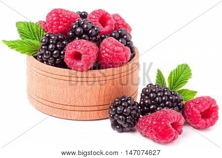 blackberries and raspberries spilled from wooden bowl isolated on white background.