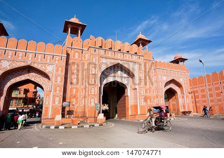 JAIPUR, INDIA - JAN 24, 2015: Ajmer gate of historical Pink City wall and moving cyclist under blue sky on January 24, 2015. Jaipur with population 6664000 people is a capital of Rajasthan