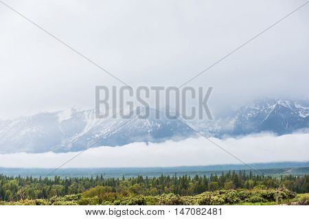 Grand Teton mountains with lake reflection and dark storm clouds overcast in national park