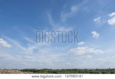 sunny sky with some clouds over wide horizon
