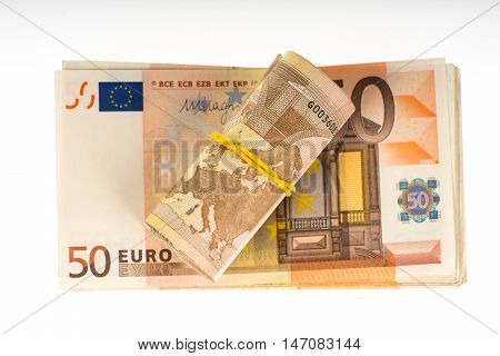 Rolled up euros with rubber on the fifty euro banknotes pile. Money bunch stack