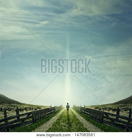 Man walking on a country road with a relax mood following a light. Way of life concept