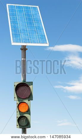 Road traffic light powered by electricity generated from a solar panel. Blue sky