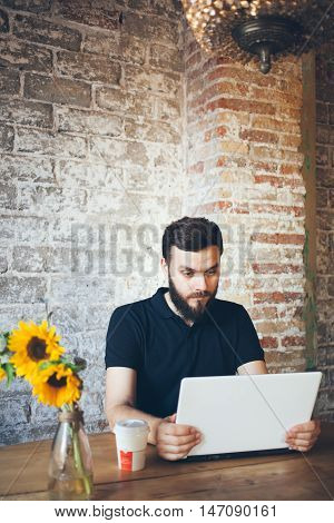 Young beard man is speaking with his family using web camera and messanger on the laptop while sitting in a nice loft cafe. Computer and communication concept
