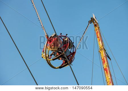 Having fun on reverse bungee in amusement park at a carnival / folk festival