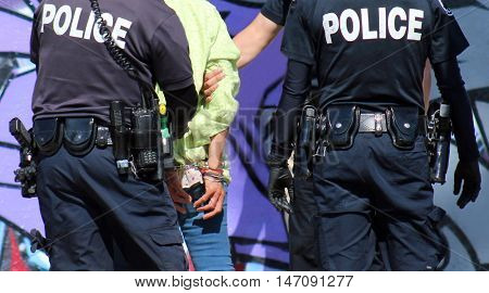 Los Angeles, California--September 5, 2016. Homeless woman arrested by police officers and handcuffed.  Confrontations between transients and police on the rise as homeless population increases.