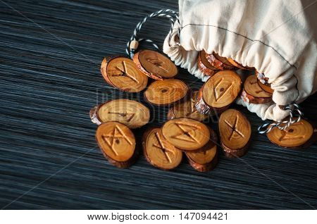 on a dark background from the rag bag spilled a few wooden runes
