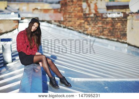 Fearless young girl sitting on an iron roof on a blurred background of old brick walls.