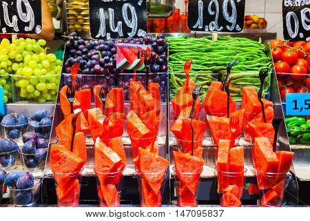 Colourful fruit, figs and vegetables at market stall in Boqueria market in Barcelona. Batch containers with watermelon, grapes, figs close with asparagus, tomato and green pepper.