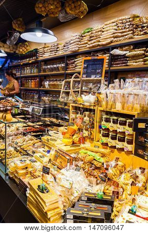 BARCELONA, SPAIN - AUGUST 25, 2016: Counter with spices and sweets at Boqueria Market in Barcelona. Shop with a variety of dried fruits, spices and honey.