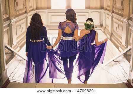 Three girls in purple dresses come downstairs a view from a back