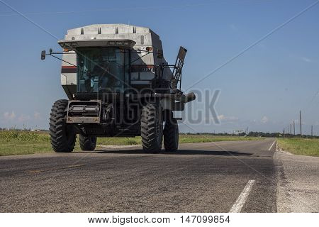 A combine harvester travels down a country road.