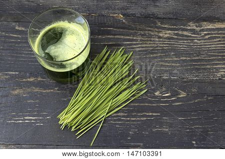 Wheat grass juice on dark wood background