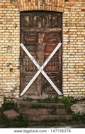 Old wooden door in a brick building boarded up crosswise