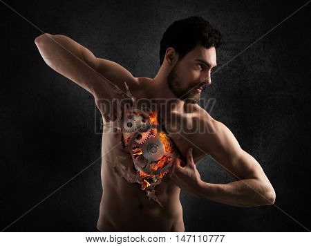 Man ripping the skin from the breast and shows a gears mechanism with fire