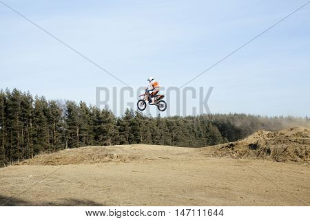 motorcycle jump from springboard outdoor training in forest, lifestyle people concept