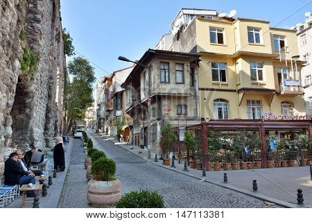 Istanbul, Turkey - November 5, 2015. Street view on Itfaiye Caddesi street in Cihangir neighborhood of Istanbul, with wall of Valens Aqueduct on the left, residential buildings, commercial properties and people.