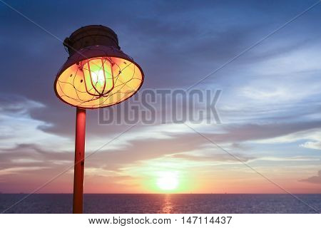 Lighting of warm lamp and lighting of sunset at sea with beautiful sky and clouds in the evening with twilight time on offshore platform.