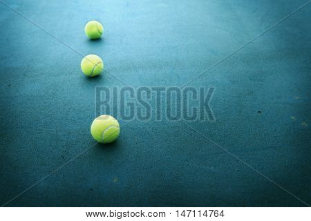 Tennis balls in line on a tennis court. Intentionally shot in surreal tone. Shallow depth of field.