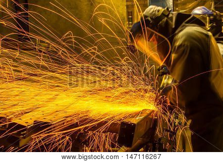 The worker grinding metal in car manufacturing plant