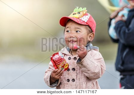 Danba China - May 2016 - China lineage Tibet kids from the villages around Danba enjoying a piece of candy on May 05 2016