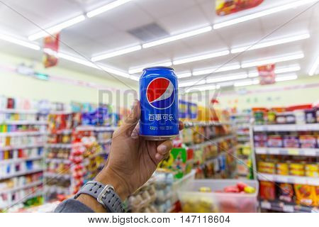 CHENGDU CHINA - MAY 8 2016: Chinese minimart store with Pepsi-Cola can in the left hand and many product inside