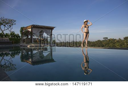 young woman walking by the pool, soaking in sun