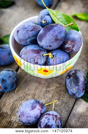Plums. Blue and violet plums in the garden on wooden table.Plums. Blue and violet plums in the garden on wooden table. Several fresh plums in a retro dish.