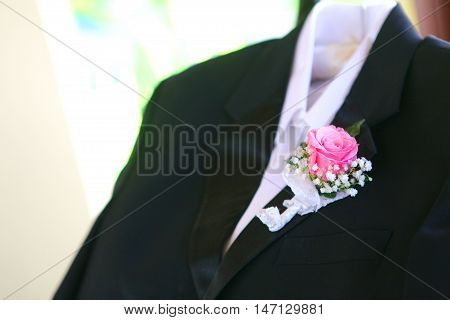 rose corsage in groom jacket for wedding ceremony