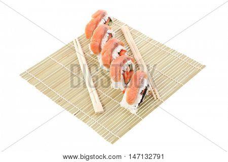 fresh japan onigiri inside out sashimi sushi on wooden bamboo mat with chopsticks isolated on white background