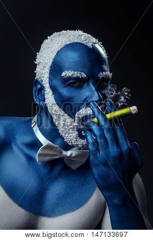 Man painted in blue color with snowy hair and beard smoking sigar on black background