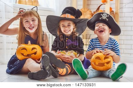 Happy brother and two sisters on Halloween. Funny kids in carnival costumes indoors. Cheerful children play with pumpkins and candy.