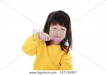 Cute Asian Girl With A Toothbrush In Hand Brush Teeth. Chinese Girl Looks Sleepy.