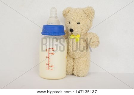 milk for baby in bottle and teddy bear