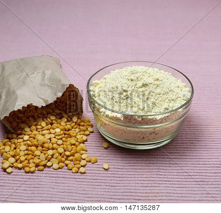 Chickpea flour, which is gluten-free, in a glass bowl and lentils spilled from a brown paper bag onto the background.