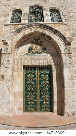The side entrance to the Temple of the Holy Sepulcher lit bright sun. Picturesque green door decorated with gold ornaments. Above the door of the golden cross and three semicircular windows