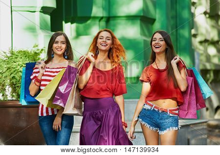 sisters triplets Women walking with Shopping Bags On City Street