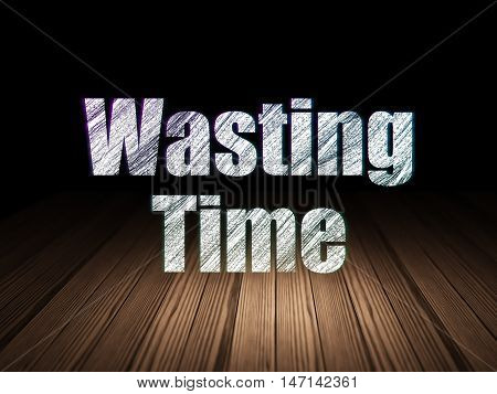 Time concept: Glowing text Wasting Time in grunge dark room with Wooden Floor, black background