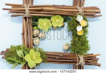 Easter frame with one boiled quail egg in the right corner and two raw plus three hellebore flowers